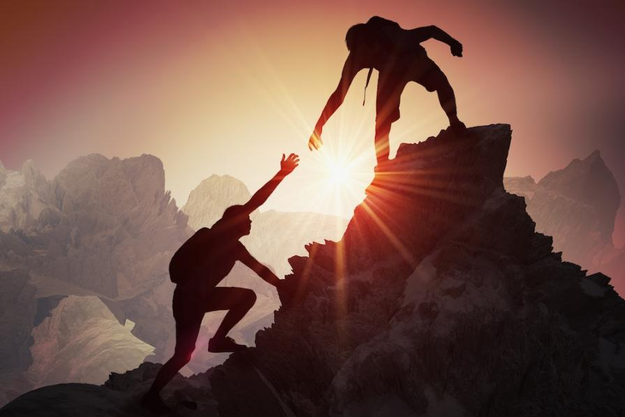 image of two people climbing a mountain representing the climb entrepreneurs must make to reach a 7 figure income