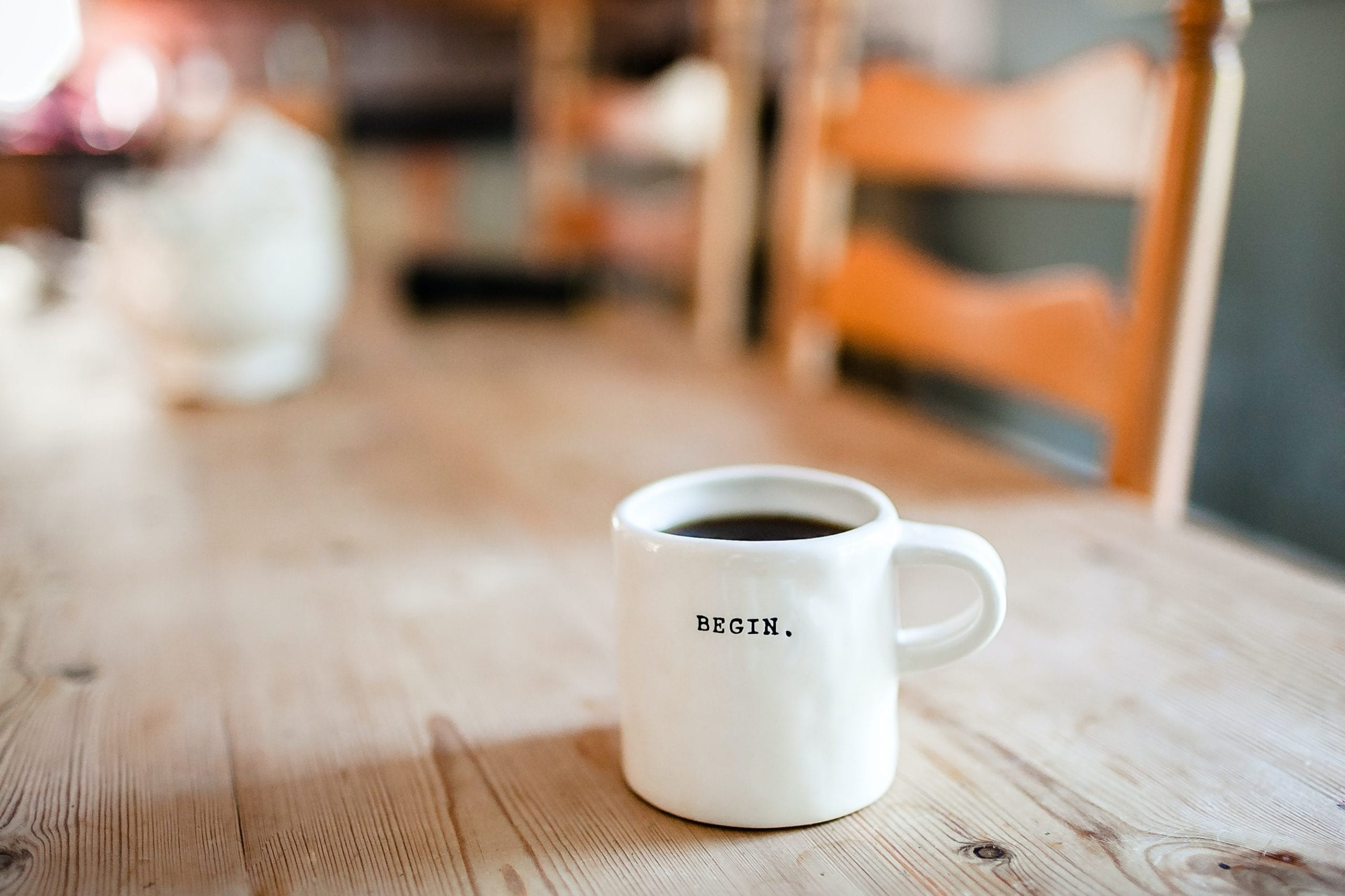 Coffee cup with the words begin on it. Beginning your online career doesn't require previous experience. James Hopkins Coaching can show you how.